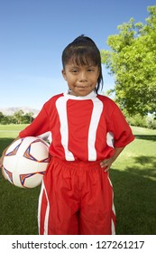 Portrait of happy young girl standing with soccer ball on field