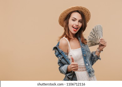 Portrait of a happy young girl in summer clothes showing money banknotes and giving thumbs up isolated over beige background