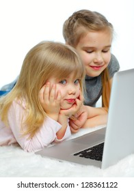 Portrait of a happy young girls with laptop computer. Vertical view. Isolated over white background