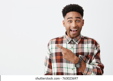Portrait of happy young good-looking tan-skinned male student with afro hairstyle in casual checkered shirt smiling, pointing aside with finger, looking in camera with excited face expression