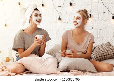 Portrait of happy young gorgeous women having nice talking in well-furnished bedroom. Sweetly smiling girls with cups of tasty beverage and soft nourishing face masks. Home beauty treatments concept