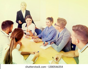 Portrait of happy young group of students listening teacher in classroom