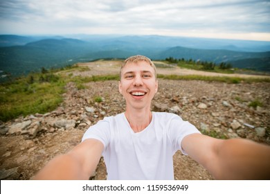 Portrait of a happy young guy making himself selfie. A cute tourist makes funny photos for a traveling blog in nature. on the top of the mountain. the concept of outdoor activities. marketing photogra