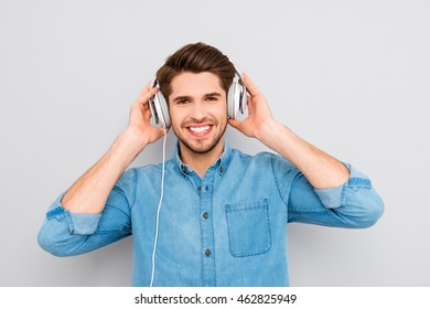 Portrait of happy young guy touching headphones and listening music