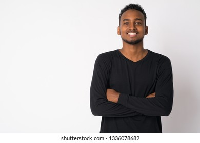 Portrait of happy young handsome African man smiling with arms crossed