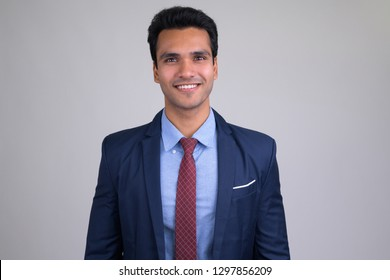 Portrait of happy young handsome Indian businessman smiling