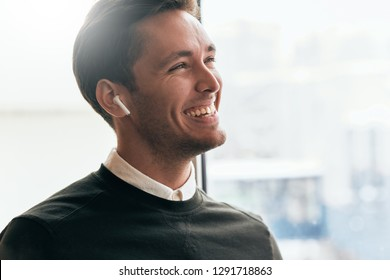 Portrait of happy young handsome man speaking with a friend telling good news using wireless earphones. Positive Caucasian businessman using wireless headphones during conversation.