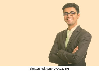 Portrait of happy young handsome Persian businessman with eyeglasses
