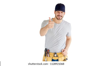 Portrait of happy young handyman giving thumbs up while standing at isolated white background with copy space.