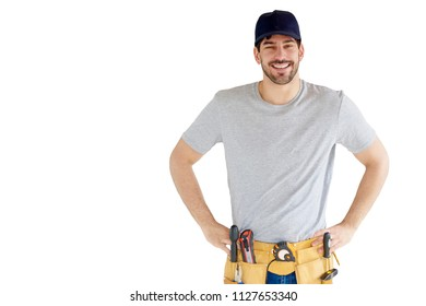 Portrait of happy young handyman with hands on his hip wearing tool belt and baseball cap while standing at isolated white background.