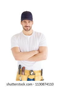 Portrait of happy young handyman standing with arms crossed at isolated white background with copy space. Successful repairman wearing baseball cap and tool belt.
