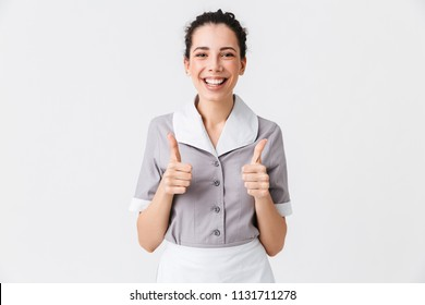 Portrait of a happy young housemaid dressed in uniform showing thumbs up gesture isolated over white background