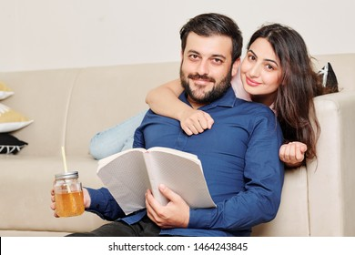 Portrait of happy young Indian couple with opened book and glass of lemonade looking at camera