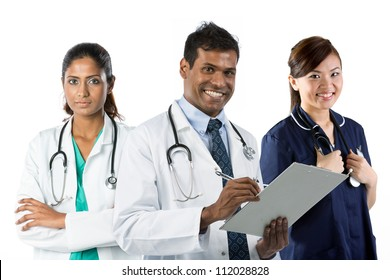 Portrait of happy young Indian doctor holding clip[ board with his team in background.
