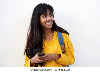 Portrait of happy young Indian woman with mobile phone and bag by isolated white background