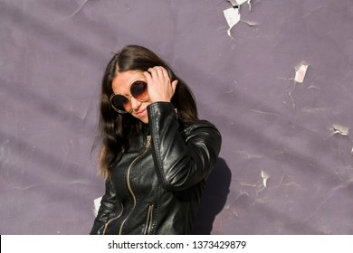 portrait of happy young latin american woman with big round sunglasses