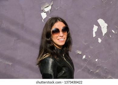 portrait of happy young latin american woman with big round sunglasses on the street
