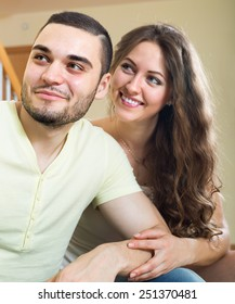 Portrait of happy young lovers in the living room at home