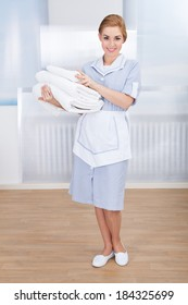 Portrait Of Happy Young Maid Holding Towels