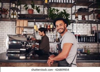 Portrait of happy young male coffee shop owner standing with barista working behind the counter making drinks.