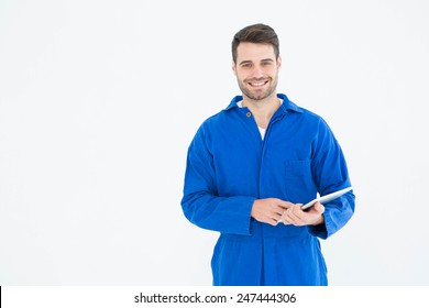 Portrait of happy young male mechanic using digital tablet on white background