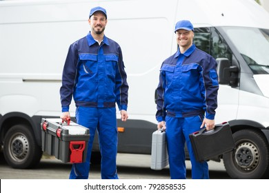 Portrait Of A Happy Young Male Worker Holding Toolbox