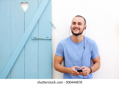 Portrait of a happy young man with beard listening to music on mobile phone