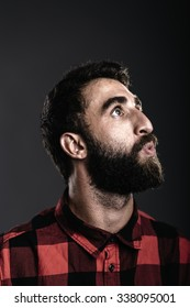 Portrait of a happy young man with beard whistling against gray background