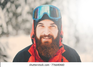 Portrait of happy young man with beard in snowy forest. Smiling man with beard in winter time. Winter mood. Sport man hiking in mountains. winter sport.