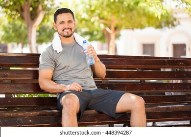 Portrait of a happy young man drinking some water from a bottle while sitting and resting in a park bench after doing some jogging outdoors