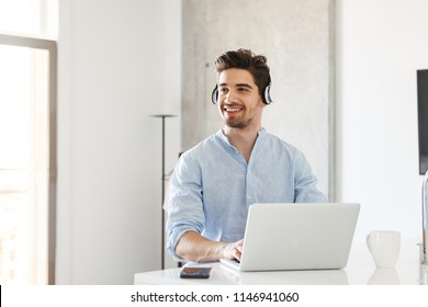 Portrait of a happy young man in earphones using laptop computer while sitting at home
