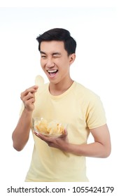 Portrait of happy young man eating potato chips and looking at camera