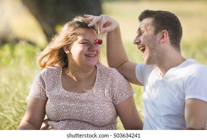 Portrait of happy young man feeding his girlfriend with cherries on picnic at park