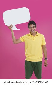 Portrait of happy young man holding speech bubble over pink background