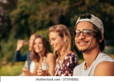 Portrait of happy young man at a lake with friends sitting by. Young friends hanging out at the lake.