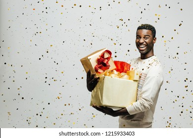 Portrait of a happy young man laughing and holding gold and red gifts as golden confetti are falling, isolated ion a gray studio background