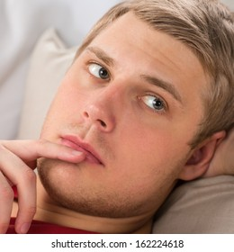 Portrait of a happy young man laying on sofa in thought