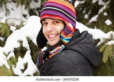 Portrait of a happy young man near a tree in winter