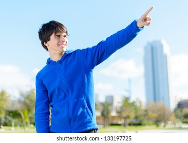 Portrait Of A Happy Young Man Pointing; Outdoors