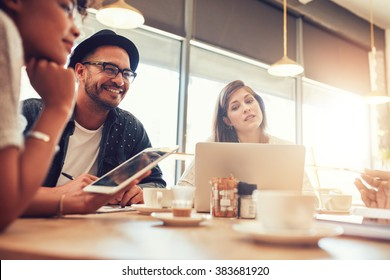 Portrait of happy young man sitting and talking with friends at a cafe. Young people at a coffee shop with digital tablet and laptop.