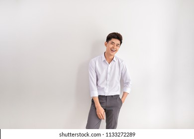 Portrait of happy young man standing against white background. Asian man with hands in pocket leaning against white wall