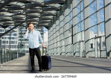 Portrait of a happy young man standing inside building with suitcase and mobile phone