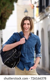 Portrait of happy young man standing on city street with bag