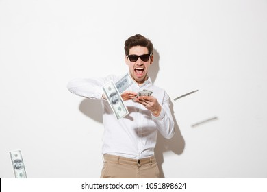 Portrait of a happy young man in sunglasses throwing money banknotes at camera isolated over white background