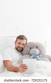 Portrait of a happy young man with a teddy bear while resting on a bed at home