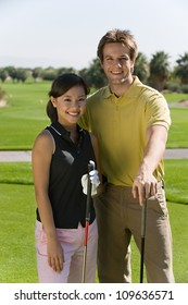 Portrait of happy young man and woman holding golf clubs on golf course