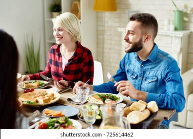 Portrait of happy young man and woman sitting at table with delicious meals, enjoying festive dinner with friends at home gathering