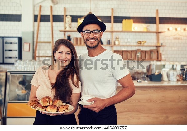 Portrait of happy young man and woman with food and cafe at coffee shop. Couple having food in a restaurant.