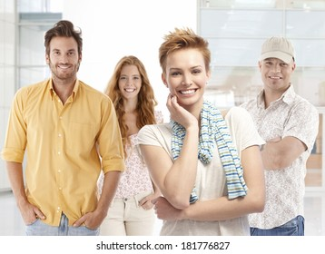 Portrait of happy young men and women, smiling, looking at camera.