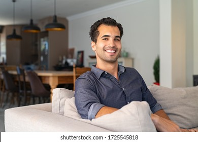 Portrait of happy young middle eastern man sitting on sofa at home. Handsome latin man in casual relaxing on couch in bright living room. Cheerful smiling mixed race guy looking at camera.